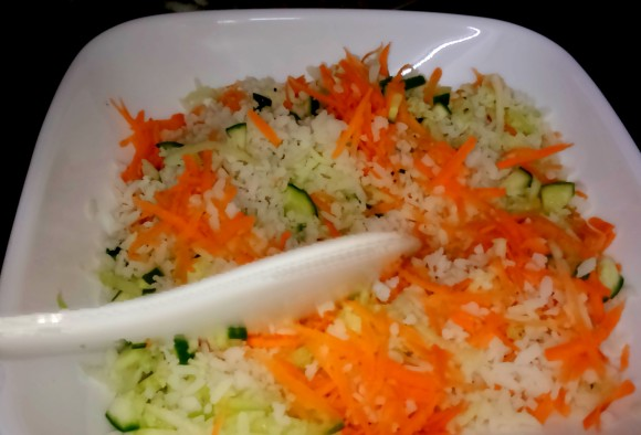 mixing poha with cucumber and carrot