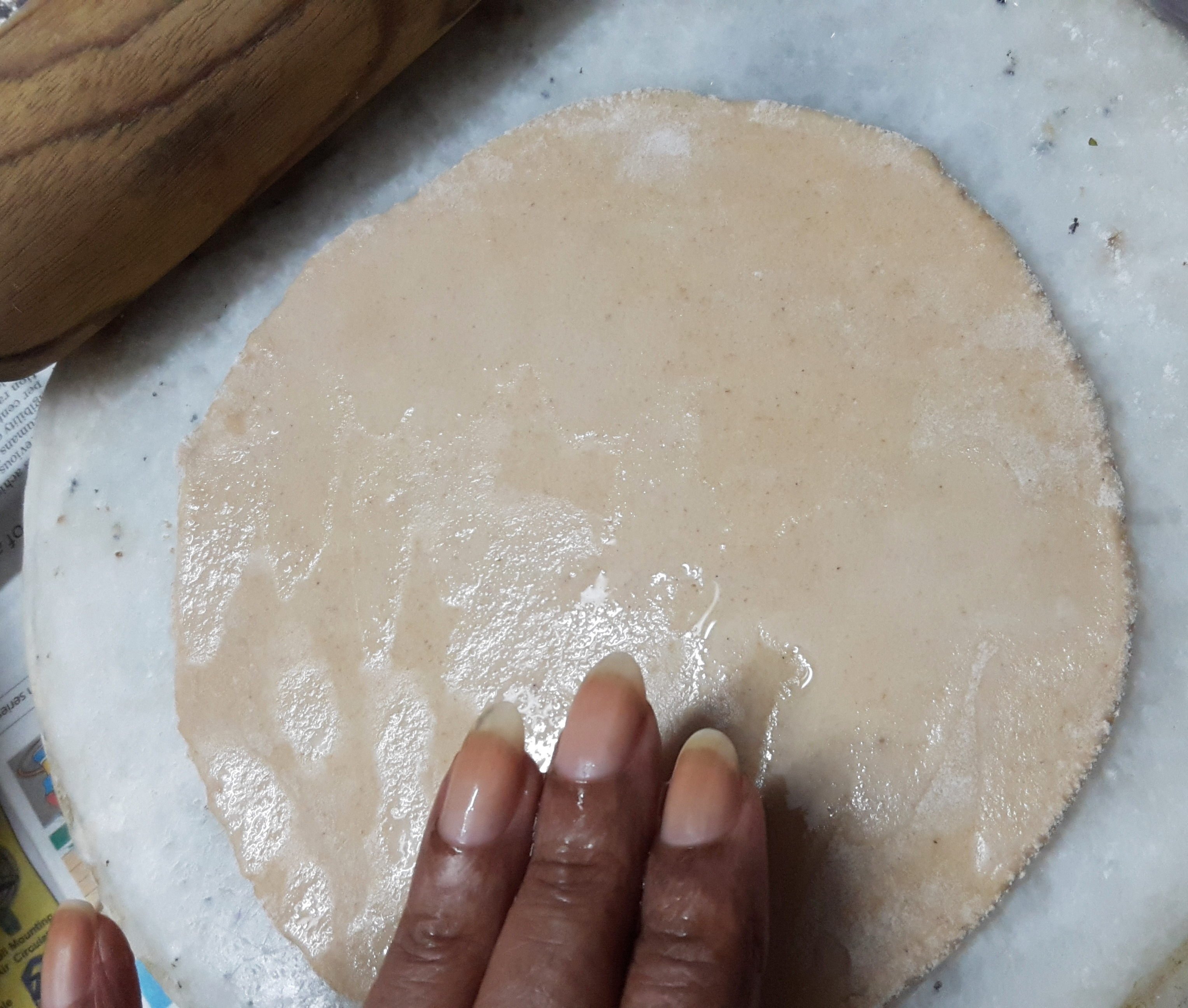 with wet hands moist the roti