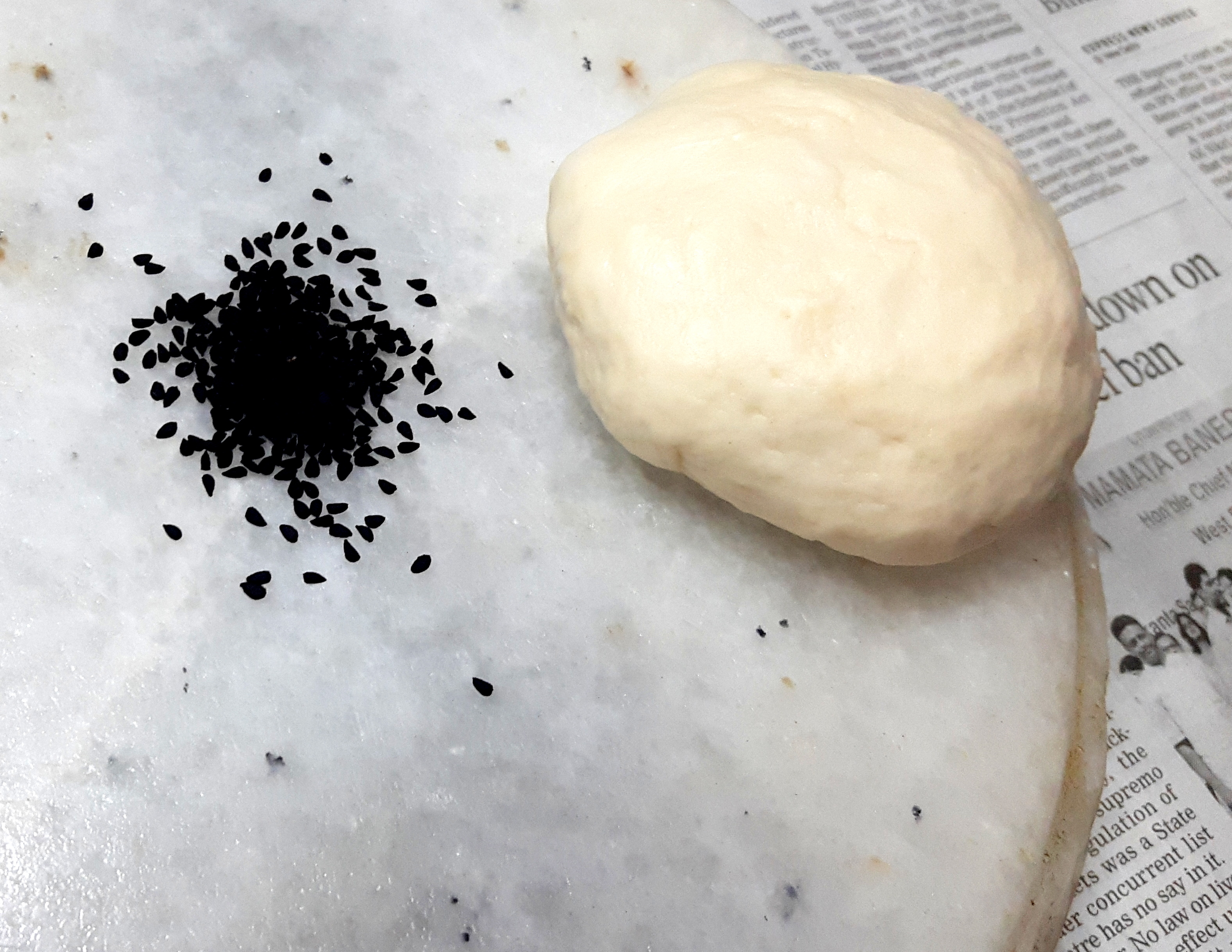 . Put (sprinkle) Kalonji (poppy seeds) on the rolling stone