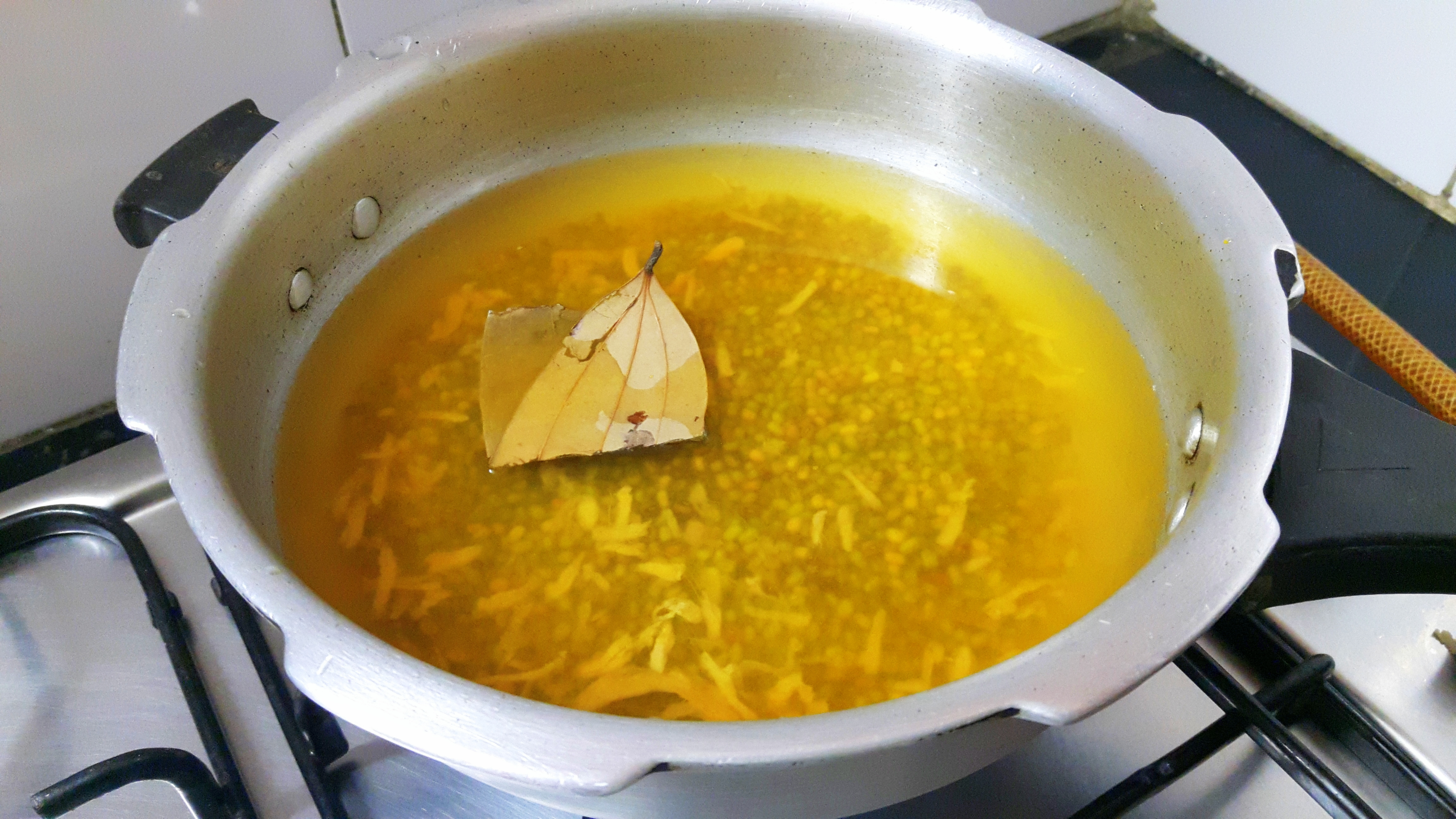 Boil soaked Mung with salt, turmeric powder, chopped ginger, bay leaf and double quantity of water